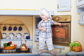 Little boy stand on a kitchen table and plays the cook — Stock Photo