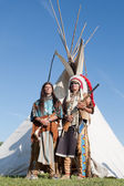 Two North American Indians stand near a wigwam — Stock Photo