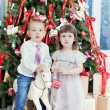 Stock Photo: Small boy and the girl play near a beautiful Christmas fir-tree