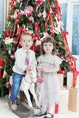 Small boy and the girl play near a beautiful Christmas fir-tree — Foto de Stock