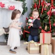 Stock Photo: Children play near Christmas fir-trees