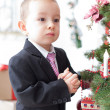 Boy decorate a Christmas tree — Stock Photo