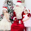 Saint Nicolas embraces two girls near a New Year tree — Stock Photo
