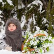 Little girl in a winter wood with the big basket of snowdrops — Stock Photo #37389429
