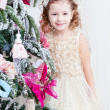 Little girl decorates a Christmas Christmas tree — Stock Photo #37389439
