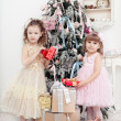 Two little girls with gifts near a Christmas fir-tree — Stock Photo