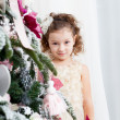 Little girl decorates a Christmas tree — Stock Photo #37389505