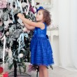 Stock Photo: Little girl decorates a Christmas tree