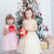 Stock Photo: Two little girls with gifts near a Christmas fir-tree