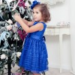Little girl decorates a Christmas tree — Stock Photo