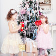 Two little girls with gifts near a Christmas fir-tree — Stock Photo #37389577