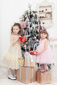 Two little girls with gifts near a Christmas fir-tree — Stok fotoğraf