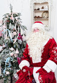 Saint Nicolas sits near the Christmas fir-tree — Stock Photo