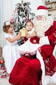Saint Nicolas gives to small children Christmas gifts — Stock Photo
