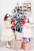 Two little girls with gifts near a Christmas fir-tree — Стоковое фото