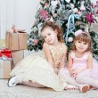 Two girls sit near a Christmas fir-tree — Stock Photo #37779503