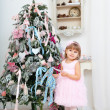 Little girl decorates a Christmas Christmas tree — Stock Photo #37779521