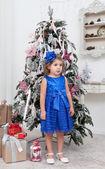 Little girl in a blue dress near a Christmas fir-tree — Foto Stock