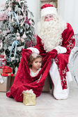 Little girl looks out of a bag with Santa Nicolai's gifts — Stock Photo