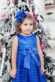 Little girl in a blue dress near a Christmas fir-tree — Stock Photo