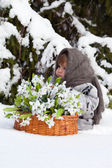 Little girl in a winter forest with the big basket — Stock Photo