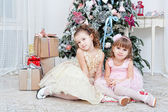 Two girls sit near a Christmas fir-tree — Stock Photo
