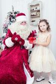Saint Nicolas gives Christmas gifts to the little girl — Zdjęcie stockowe