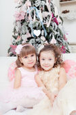 Two girls sit on a sofa near a Christmas fir-tree — Stockfoto