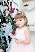 Child with a toy hare near a Christmas fir-tree — Stock Photo