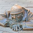Cumil - statue of man peeking out from under a manhole cover — Stock Photo #40076421
