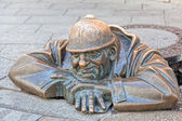 Cumil - statue of man peeking out from under a manhole cover — Stockfoto