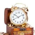 guld väckarklocka låg på pengar i en trä bröst — Stockfoto #41113325