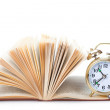 Alarm clock to stand on the open book — Stock Photo