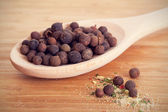 Allspice in a wooden spoon on a table — Stock Photo