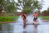 Young people skip astride horses — Stock Photo