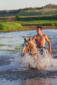 Rider on horse down the river — Stock Photo