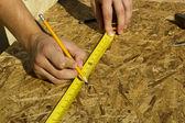 Arbeitnehmer, die messung von sperrholz — Stockfoto