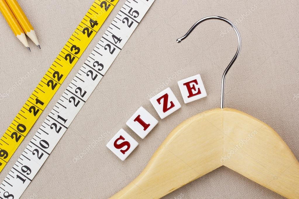 "Close-up photograph of a wooden hanger and measuring tape next to the word ""size"" on a gray background. — Stock Photo #12659921"
