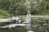 Stone sculpture of a priest on the water — Stock fotografie