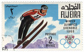 Ski jumper at the Winter Olympics in Grenoble on postage stamp — Stock Photo