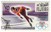 Running skater at the Winter Olympics in Grenoble on postage sta — Stock Photo