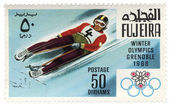Descent to sledge at the Winter Olympics in Grenoble on postage — Stock Photo