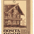 Old wooden house in northern village on post stamp — Stock Photo
