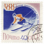 Skier on a steep mountain slope on post stamp — Stock Photo
