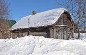 Alte log-hütte, die mit schnee bedeckt — Stockfoto
