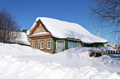 Wooden house and a car in snow drifts — Stock Photo