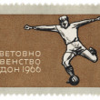 Football player kicks the ball on post stamp — Stock Photo