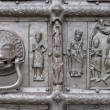 Door knocker and bas-relief of ancient bronze gate — Stock Photo