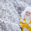 Beautiful girl in a white fluffy hat on snow — Stock Photo