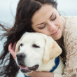 Portrait of beautiful young woman playing with dog on the sea — Stock Photo